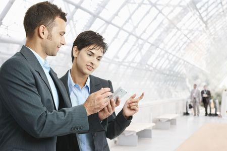 Dos empresarios de pie en el pasillo, mirando de teléfono móvil, sonriendo.