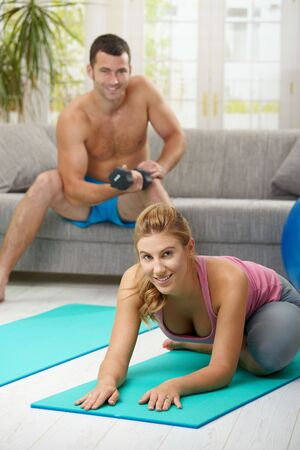 Young women streching lying on fitness mat, muscular man doing biceps exercise in background. Selective focus on woman. photo