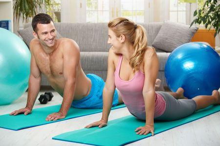 abdomen fitness: Joven pareja acostado en el colch�n de aptitud y streching abdominal. Mirando cada uno por el otro, sonriendo. Foto de archivo