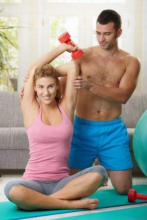 Couple doing dumbbell exercise sitting on fittness mat at home, smiling. photo
