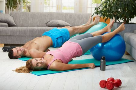 abdominal muscles: Young couple doing abdominal exercise with fit ball in living room, smiling.