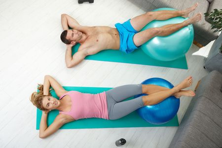 Young couple doing abdominal crunch using fit ball at home,\ overhead shot.