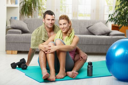 Young couple resting after training, sitting on fitness mat in living room, smiling. photo
