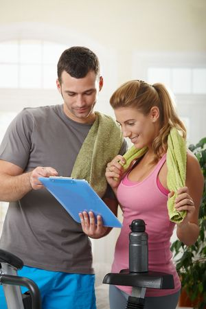 personal trainer: Young woman checking training plan with her personal trainer standing beside exercise bike at home.
