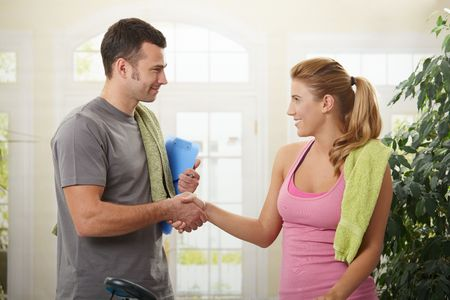 Young woman shaking hands with her personal trainer after training. photo