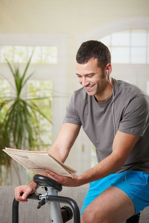home gym: Man sitting on stationary bike at home, reading newspaper and listening music.