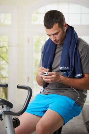 gym room: Man sitting on stationary bike at the end of training and using smart phone. Stock Photo