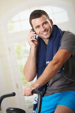 home gym: Man sitting on stationary bike after training and talking on mobile phone.