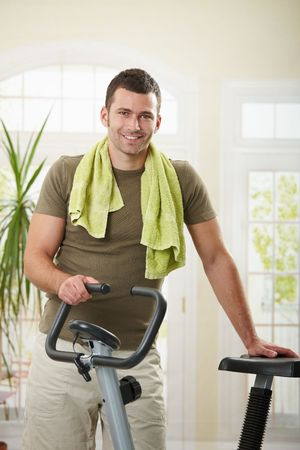 stationary bicycle: Man wearing sportswear and towel standing in living room at home with training bike, smiling.