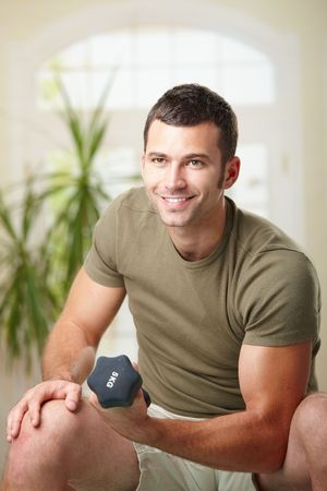 Muscular man doing biceps exercise at home with hand barbell, smiling. photo