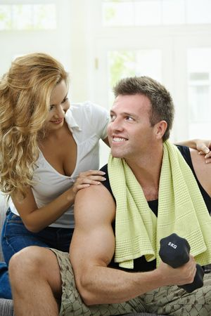 Muscular man sitting on sofa at home, doing excercise with hand barbell, her girlfriend embracing from behind. photo