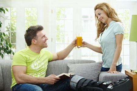 jambe cass�e: Man Rasting cass? la jambe dans le pl?tre sur le canap? ? la maison, lecture de livres. Femme lui apporter du jus d'orange.