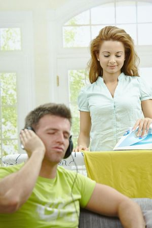 Husband sitting at couch listening music, wife ironing in the background, smiling. Selective focus on woman. photo