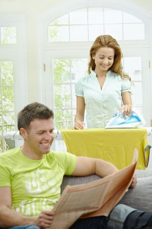 Husband sitting at couch reading news, wife ironing in the background, smiling. Selective focus on woman. photo