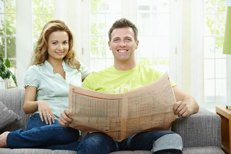 Happy couple reading newspaper together on couch at home, looking at camera, smiling. photo