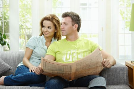 Love couple reading newspaper together on couch at home, smiling. Stock Photo - 6308343