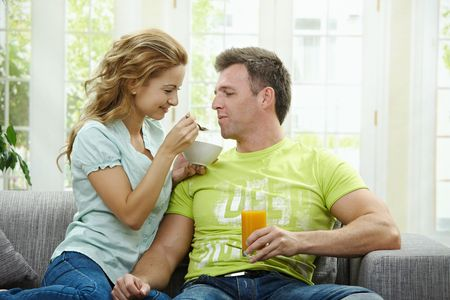 Love couple eating breakfast cereal together, sitting on couch at home. photo