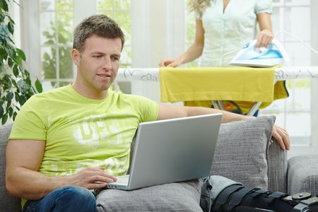 Man with broken leg resting on couch, using laptop computer. Woman doing ironing at the background. photo