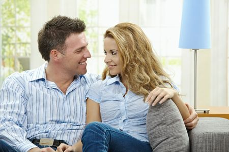 couple cuddling: Portrait of happy couple sitting on sofa embracing, looking at camera and smiling.  Stock Photo