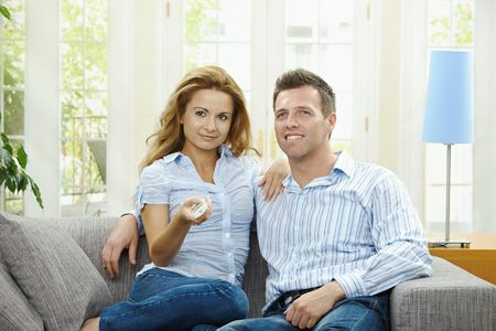 Young couple watching TV at home, sitting on couch, holding remote control in hand. photo