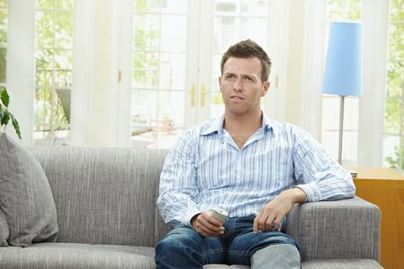 1 man only: Man watching TV at home, sitting on couch, holding remote control in hand. Stock Photo