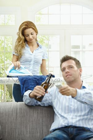 Husband sitting at couch watching TV, wife ironing in the background, smiling. Selective focus on woman. Stock Photo - 6308377
