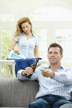Happy man sitting at couch watching TV, woman ironing in the background. Selective focus on man. Stock Photo - 6308324