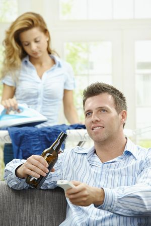 Happy man sitting at couch watching TV, woman ironing in the background. Selective focus on man. Stock Photo - 6308374