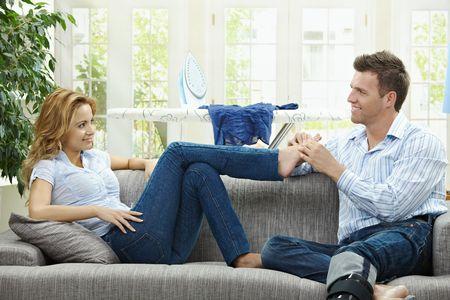 buen vivir: Masaje de pareja relajante en casa en sof�, hombre, dando pie a su gildfriend.