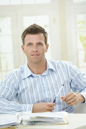 Man working at home, sitting at table in living room.