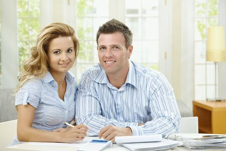 living together: Happy couple sitting at home, planning household financials. Stock Photo