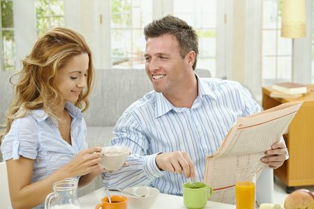 Couple having healthy breakfast at home, eating cereals drinking coffee, and reading newspaper. Stock Photo - 6308345