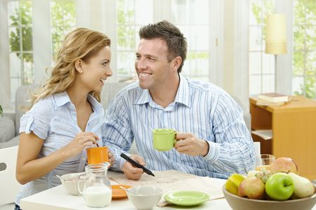 Happy couple drinking coffee at home, sitting at breakfast table, looking at each other, smiling. Stock Photo - 6308341