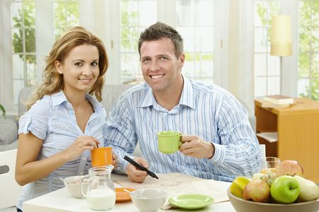 Couple drinking coffee at home, sitting at breakfast table, marking newspaper. photo