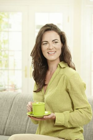 Happy young woman drinking coffee, sitting on couch in living room, smiling. photo
