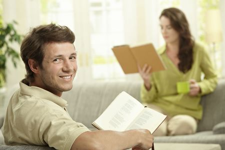 Happy couple reading book sitting at home on couch. Selective focus on man, looking at camera, smiling. photo