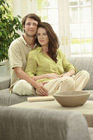 Young couple sitting together on couch at home, embracing, smiling. photo