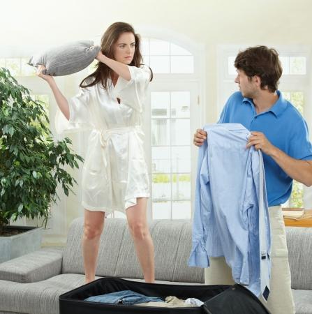 personas discutiendo: Infeliz par de combates. Mujer golpear el hombre que es de embalaje su ropa con una almohada. Foto de archivo