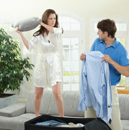 Unhappy couple fighting. Woman hitting man who is  packing his clothes with a pillow. photo
