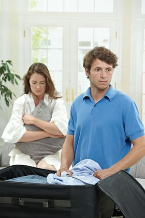 Unhappy couple breaking. Man packing his clothes into suitcase, sad woman hugging pillow in the background. Selective focus on man. photo