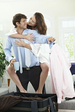 cuddling: Happy couple packing for business trip at home in the morning, embracing and smiling.