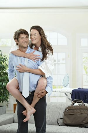 Happy young businessman holding his girfriend, smiling. photo