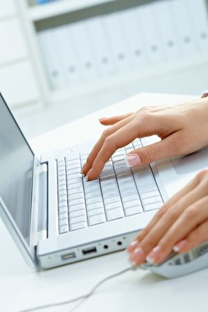 Closeup picture of female hands using laptop computer and mouse. Stock Photo - 6307175