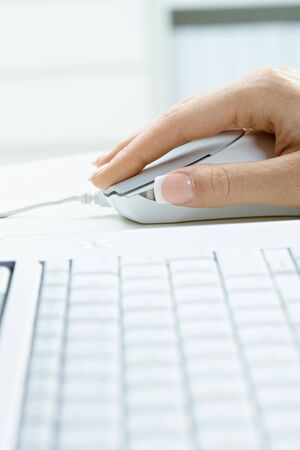 using computer: Closeup picture of computer keyboard and female hand using mouse. Stock Photo