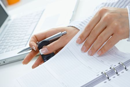 Female hands holding pen and turning a page of personal organizer. photo