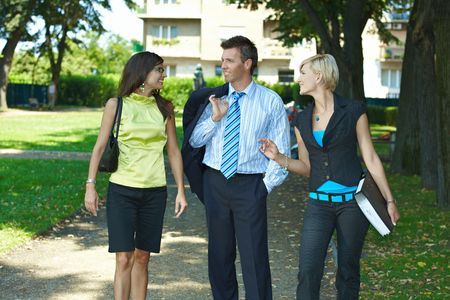 open collar: Young businesspeople walking and talking in downtown park.