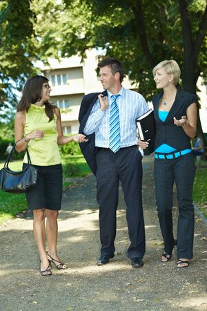 attire: Young businesspeople walking and talking in downtown park.
