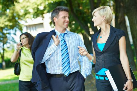 attire: Businessman and businesswoman walking and talking in downtown park.