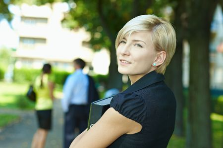 Portrait of young businesswoman standing in sunny park, smiling. Stock Photo - 6308411