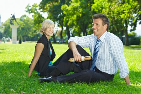 Young businesspeople sitting on grass and having lunch outdoor in city park summertime. Stock Photo - 6308427